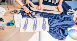 Tailors cutting blue fabric on the table